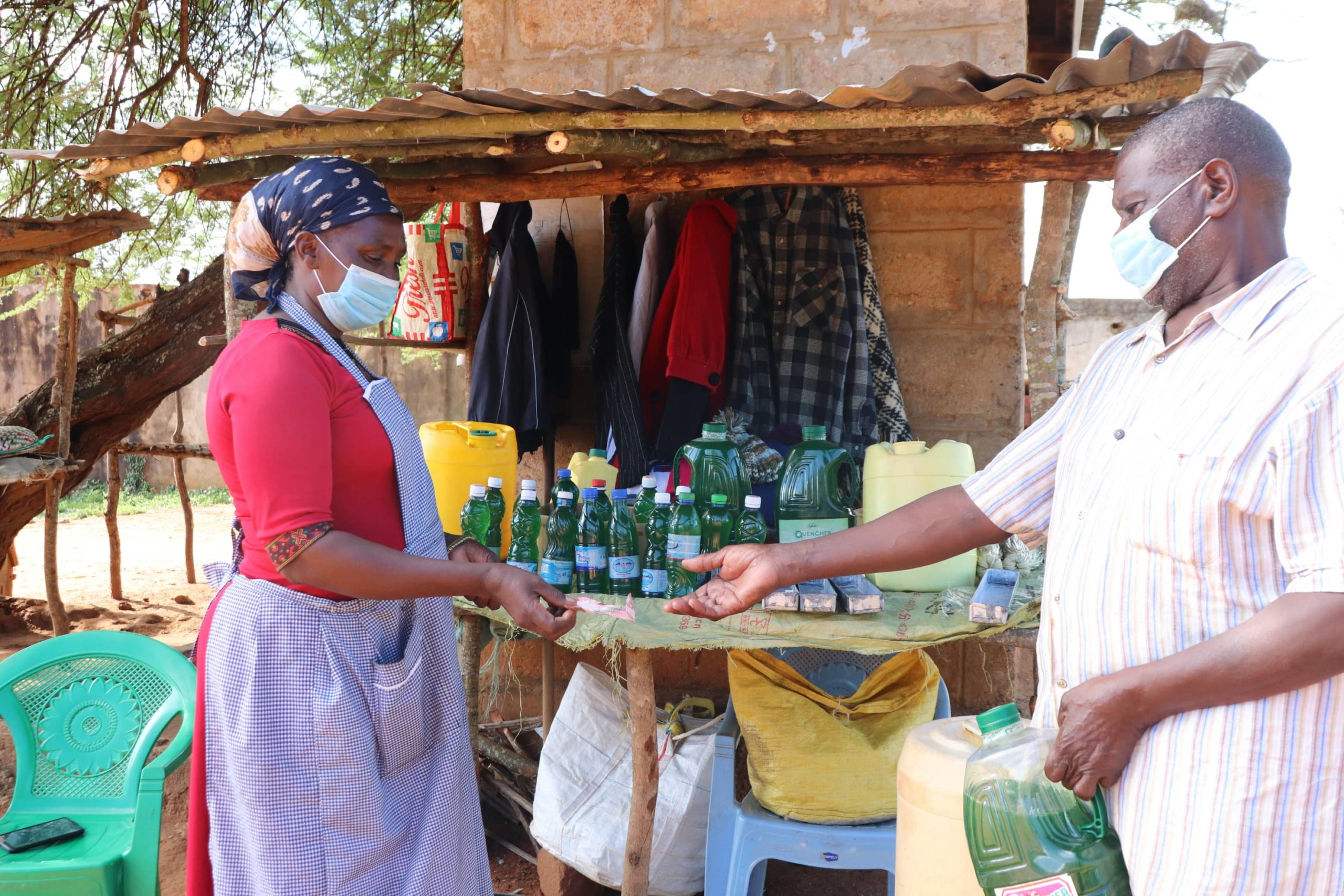 A woman in a mask sells soap to a local man.