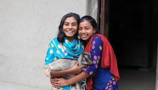 Two girls with a goat stand in front of a building in Bangladesh.